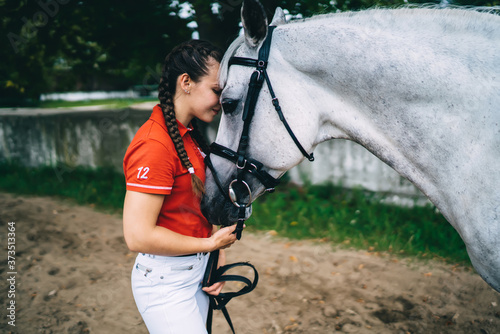 Valokuvatapetti Side view of carefree female jockey feeling calmness during weekend training wit