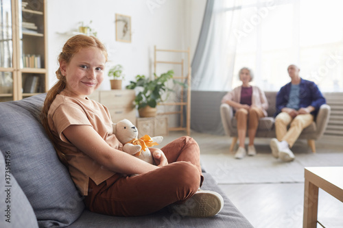 Warm toned portrait of cute red haired girl looking at camera while sitting on c Fototapeta