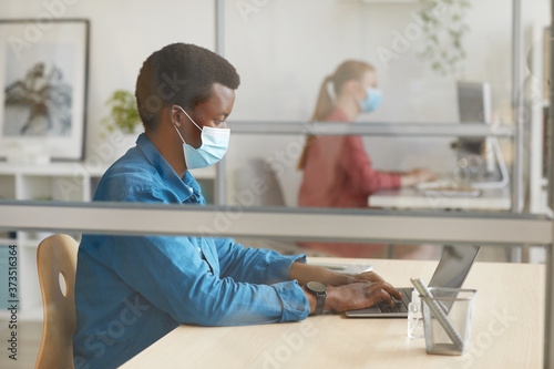 Fotografiet Side view portrait of young African-American man wearing mask and using laptop w