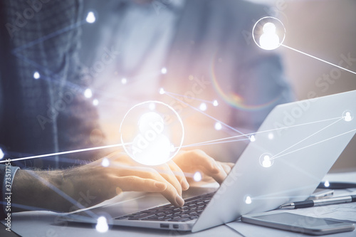 Photo Social network theme hologram with businessman working on computer on background
