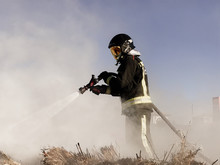 Firefighter Spraying Water On ...
