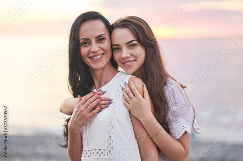 Portrait of happy attractive smiling hugging daughter and mother in summertime a Canvas Print