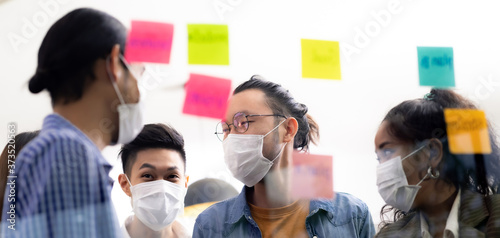 Obraz Interracial business team wear face mask brainstorm at new normal office Panorama - fototapety do salonu