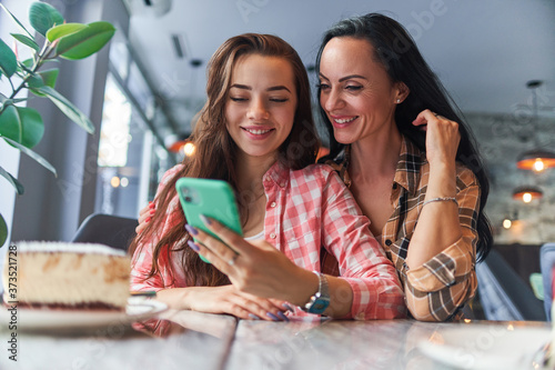 Fotografie, Obraz Happy smiling mother and joyful teenager daughter watching video content on the