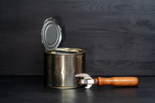 Tin Can And Old Opener On Wooden Background