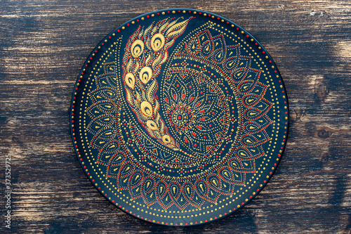 Obraz Decorative ceramic plate with black, red and golden colors, painted plate on wooden background , dot painting - fototapety do salonu