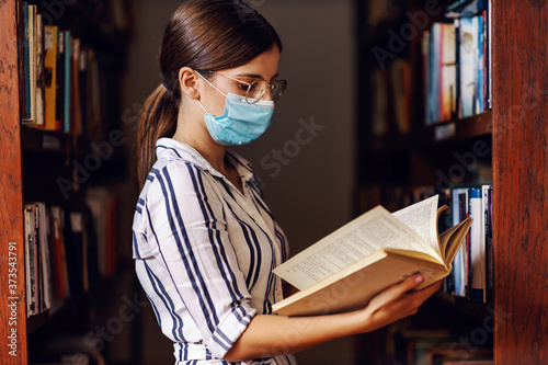 Young intelligent female student with face mask with brown hair standing in library and doing research for school project Canvas-taulu