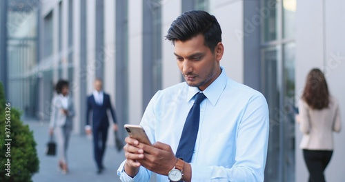 Photo Handsome Hindu young businessman in tie using smartphone and texting message at street