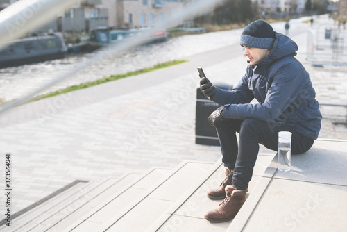 Fotografie, Obraz A man wearing boots, jacket and gloves checks his mobile phone while sitting on