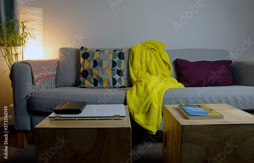 Fototapeta Cozy and relaxed interior of a living room - sofa with pillows and blanket and a