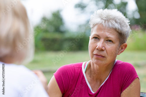 Portrait of a blonde woman in a red T-shirt listening to the interlocutor on a g Canvas Print