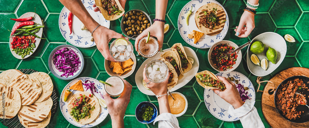 Fototapeta Friends home taco party. Flat-lay of Mexican traditional dishes Tacos with beef meat, corn tortillas , tomato salsa and peoples hands with glasses over green background, top view. Mexican cuisine