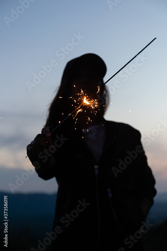 Photo silhouette of a woman with a sparkler