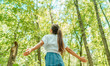 Free woman breathing clean air in nature forest. Happy girl from the back with open arms in happiness. Fresh outdoor woods, wellness healthy lifestyle concept.
