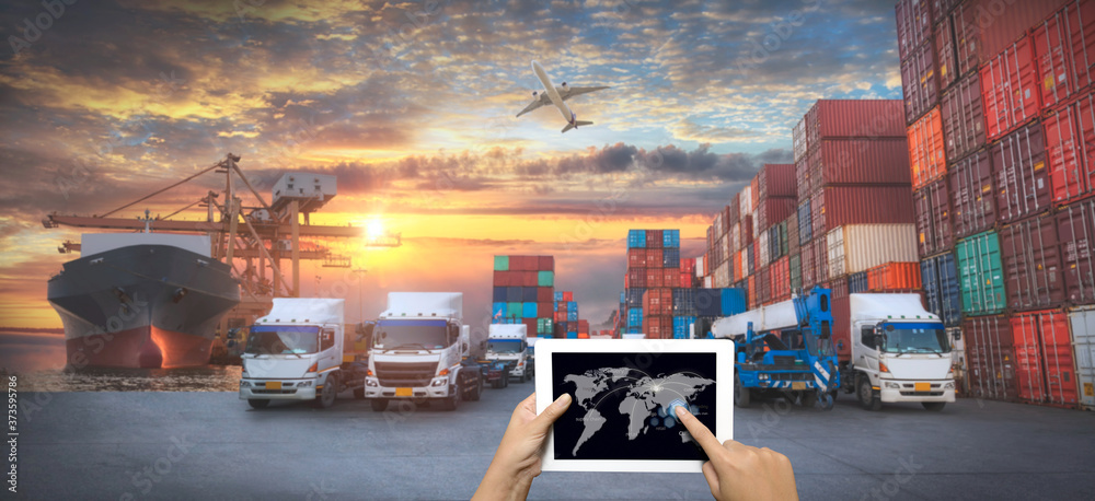 Fototapeta Hand holding tablet is pressing button on touch screen interface in front Logistics Industrial Container Cargo freight ship for Concept of fast or instant shipping, Online goods orders worldwide