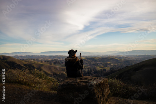 Fotografie, Tablou A woman in a hat with a hiking stick enjoying the views of the mountain landscap