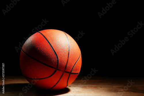 Canvas-taulu Ball for playing basketball on table against dark background