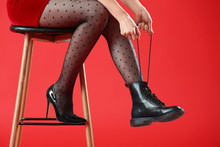 Young Woman In Different Shoes Sitting On Chair Against Color Background
