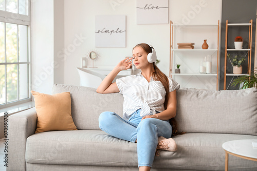 Sleepy young woman listening to music at home Poster Mural XXL