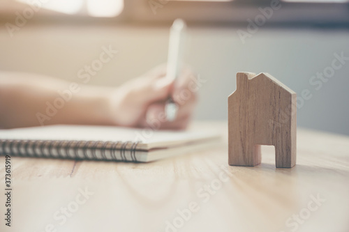 Cuadros en Lienzo Close up hand of man take notes in a notebook plan to be a landlord with wooden house model