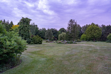 During Twilight, These Threatening Clouds Create A Distinct Atmosphere In This Beautifully Landscaped Garden With A Great Diversity Of Trees And Flowering Shrubs