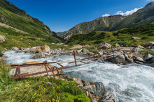 Dangerous Dilapidated Rusty Metal Bridge Over A Turbulent Mountain River On A Sunny Day, Tien Shan Mountains, Kazakhstan