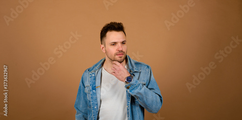 Fényképezés Handsome man standing and smiling isolated on light brown studio background