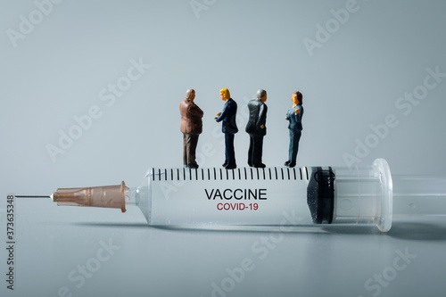 medical industry business people standing on syringe. new covid-19 virus vaccine invention concept