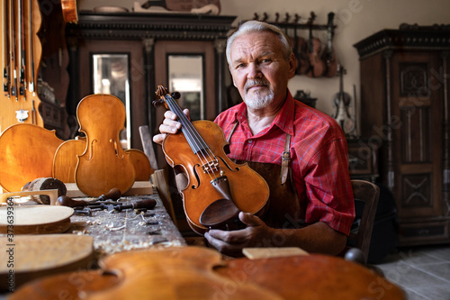 Senior carpenter showing violin instrument he created Canvas Print