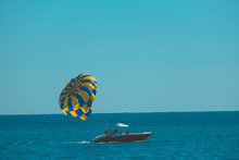 A Boat With A Parachute Rides ...