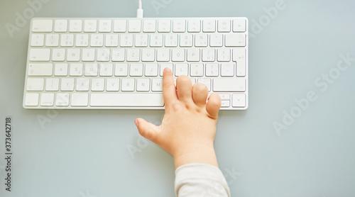 Canvastavla Kind tippt mit Zeigefinger auf Computer Tastatur