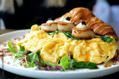 Fotografering Scrambled eggs with salad greens and seared scallops in a croissant