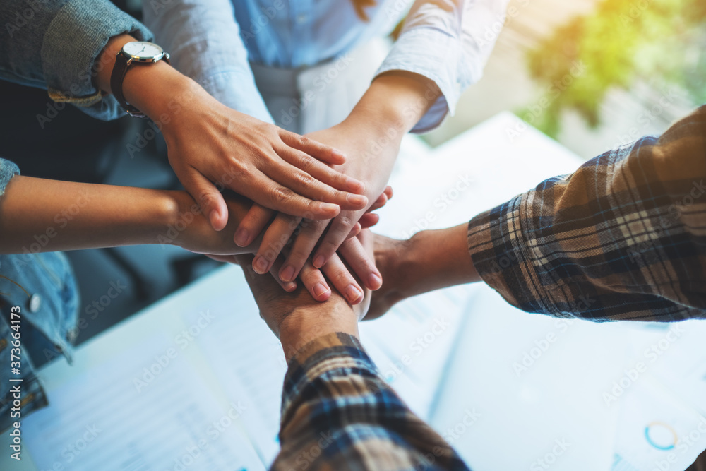 Fototapeta Closeup image of business team standing and joining their hands together in office