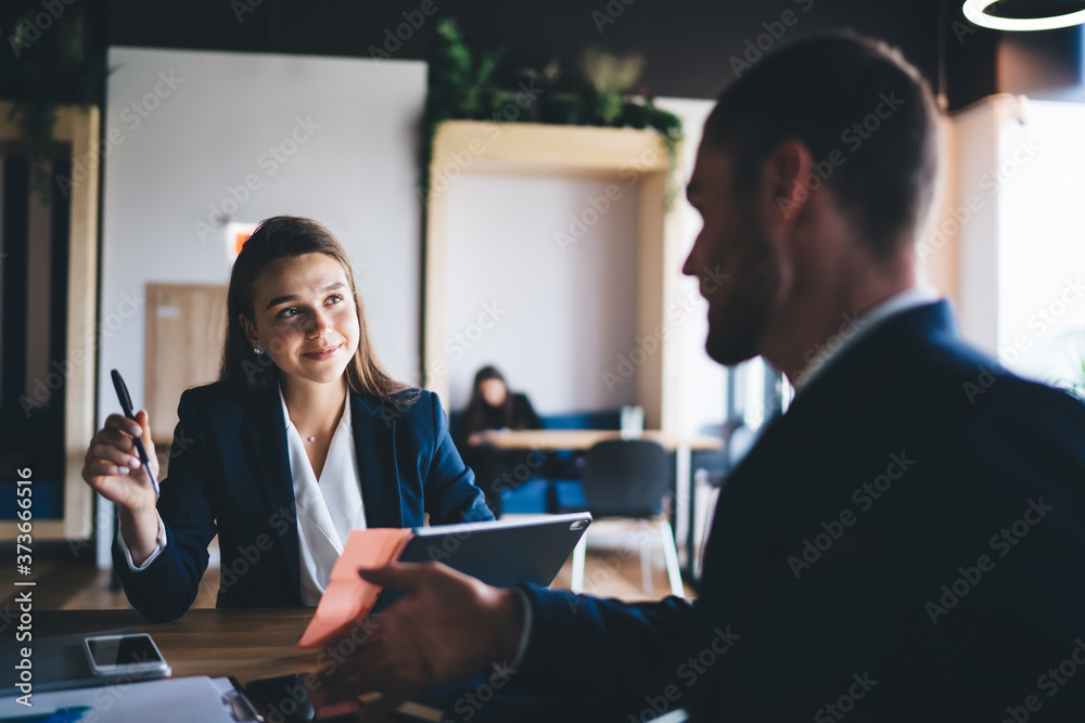 Fototapeta Young female employee listening to team leader explaining new strategy in office