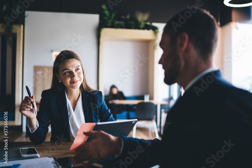 Young female employee listening to team leader explaining new strategy in office