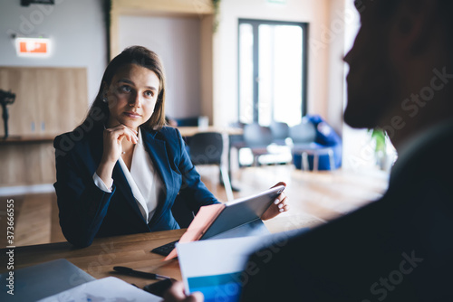 Serious young secretary listening to anonymous male boss attentively in office