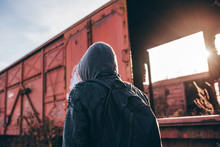 Homeless Immigrant With Hoodie Walking Among Old Train Wagons