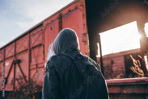 Homeless immigrant with hoodie walking among old train wagons Wallpaper Mural