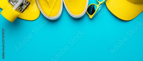 Fototapeta yellow baseball cap, sunglasses, sneakers, mini cruiser board on blue background