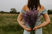 The Girl Holds In Her Hands A Large Bouquet Of Lilac And Violet Flowers Behind Back. In The Background Is Green Yellow Grass And Trees. Blue Turquoise Polka Dot Dress On A Tanned Brunette Girl.