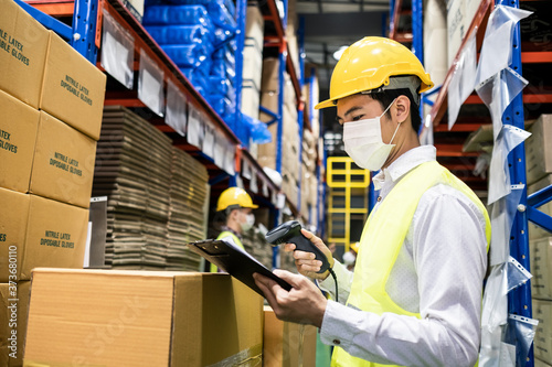 Asian male engineer worker wear mask work during COVID in warehouse.