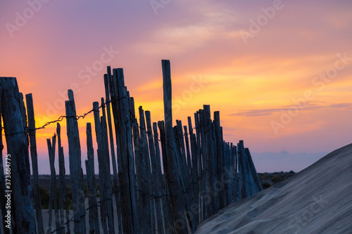 photographie d'une clôture en bois sur la plage lors du coucher de soleil en cam Wallpaper Mural