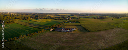 Leinwand Poster Aerial panoramic view of Dutch farm at sunset with warm colours in the blue sky