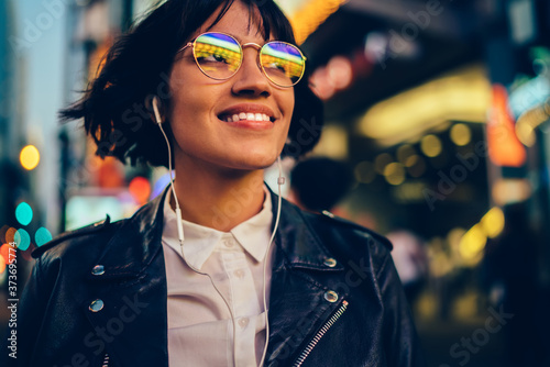 Fotomural Cheerful woman teenager in glasses with neon lights spending evening in megalopo