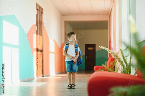 Fotografija Portrait of a schoolboy standing with a backpack on an empty school hallway