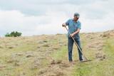 Fototapeta Krajobraz - Man in a field haymaking and reaping hay by a rake