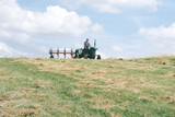 Fototapeta Krajobraz - Man operating hay tedder machine to aerate the hay in the field