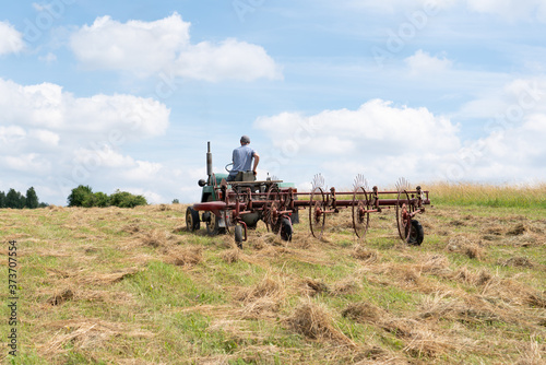 Man operating hay tedder machine to aerate the hay in the field Canvas Print