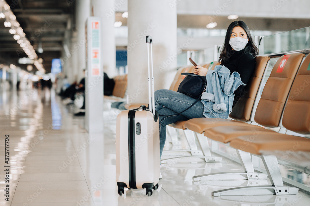 Fototapeta Asian woman tourist wearing face mask sitting on social distancing chair with luggage at airport terminal during coronavirus or covid-19 outbreak . New normal travel at airport