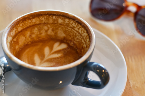Close-up view cappuccino, Drinking hot coffee in a blue cup with sunglasses background Fotobehang